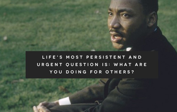"Dr. Martin Luther King, Jr. sitting in a grassy field. Text with a dark dray back-drop reads, ""Life's most persistent and urgent question is: What are you doing for others?"" followed by an attribution to Dr. King."